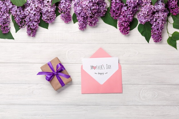 A bouquet of lilacs with cup of tea, gift box, color envelope and love note on white boards . mother's day