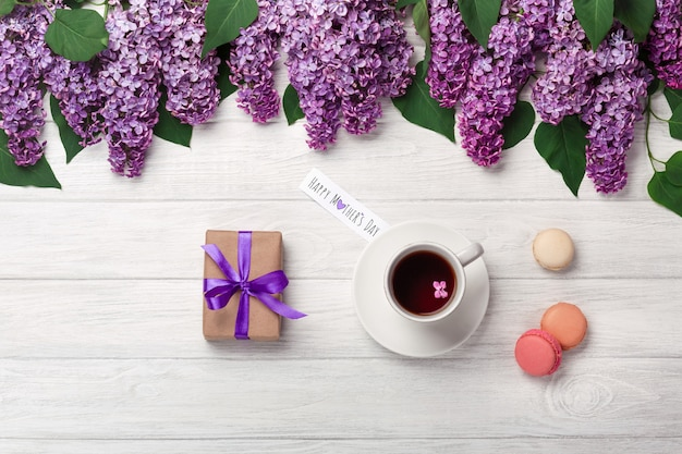 A bouquet of lilacs with cup of tea, gift box, macarons and love note on white boards . mother's day