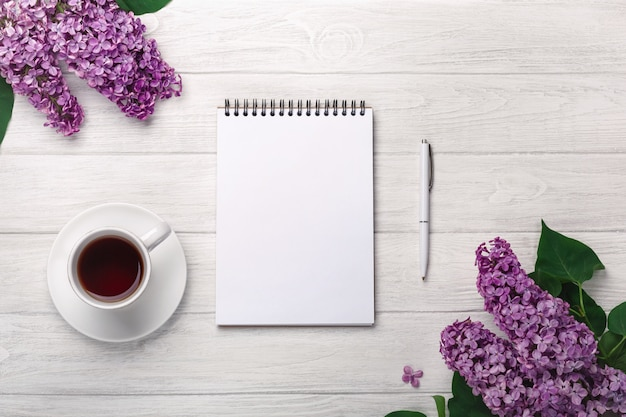 A bouquet of lilacs with cup of tea, notebook, craft envelopes on white boards . mother's day