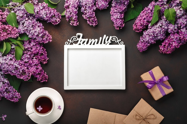 A bouquet of lilacs with cup of tea, a white frame for inscription, gift box, craft envelope, a love note on rusty background