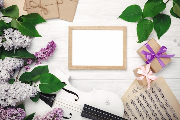 A bouquet of lilacs with violin, chalk board, gift box and music sheet on a white wooden table. top wiev with space for your text