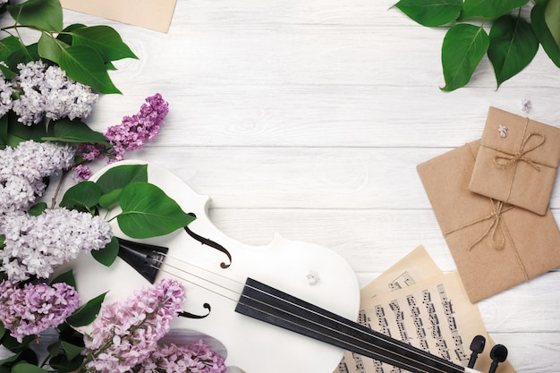 A bouquet of lilacs with violin, letter and music sheet on a white wooden table. top wiev with space for your text