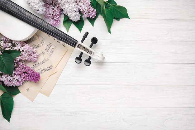 A bouquet of lilacs with violin and music sheet on a white wooden table. top wiev with space for your text.