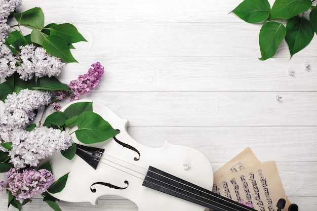 A bouquet of lilacs with violin and music sheet on a white wooden table. top wiev with space for your text