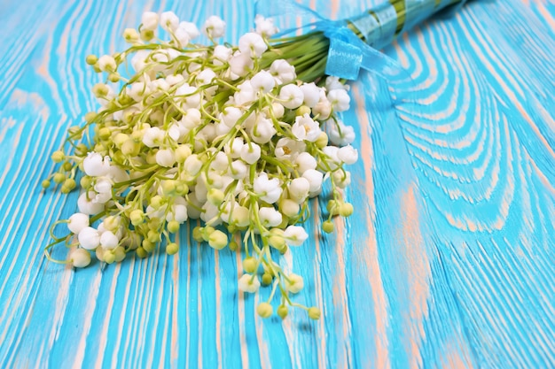 Bouquet of lilies of the valley on the blue wooden table