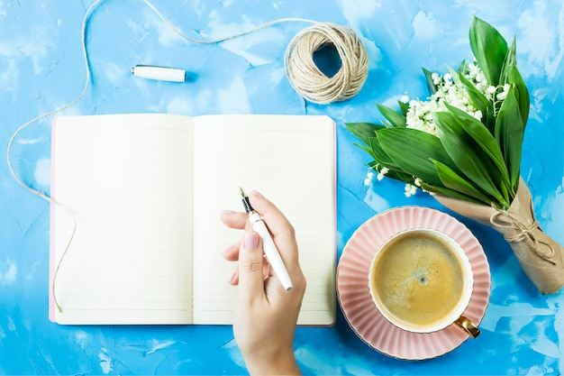 A bouquet of lilies of the valley, a cup of coffee and a notebook on a blue table