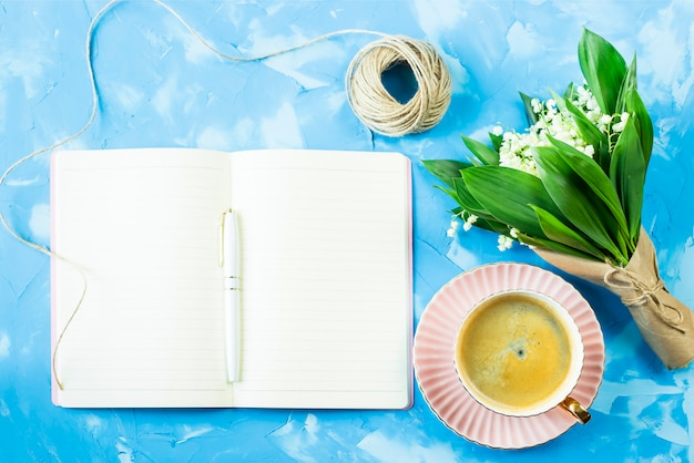 A bouquet of lilies of the valley, a cup of coffee and a notebook