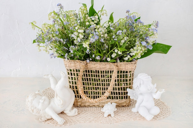 A bouquet of lilies of the valley and forget me nots in a basket on the table and three angels