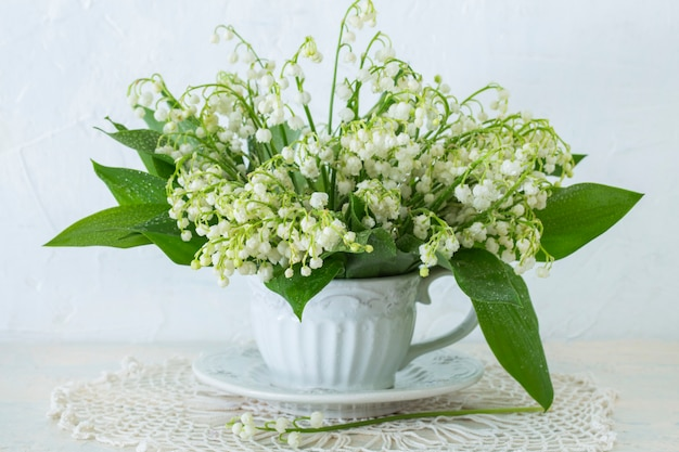 A bouquet of lilies of the valley in an old mug on the table
