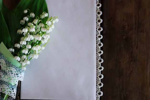 Bouquet of lilies of the valley and space text