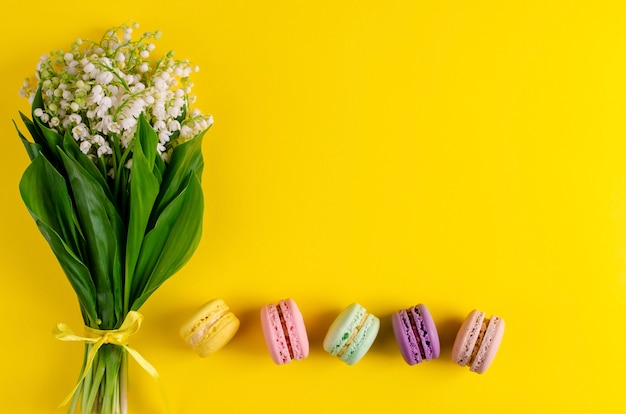 Bouquet of lilies of the valley tied with ribbon and colorful macaroons on yellow