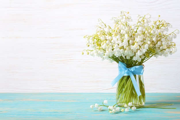 Bouquet of lilies of the valley in a vase with blue ribbon on a blue and white wooden table