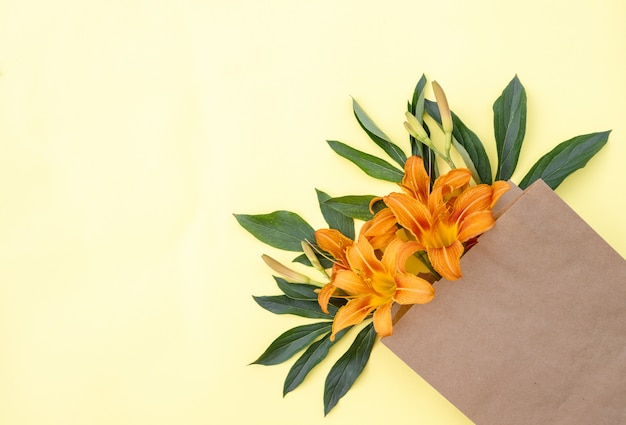 Bouquet of lily flowers in a craft bag on a yellow background. flower delivery. floral composition. space for text. spring background. flat lay. floristic. postcard for the holiday.
