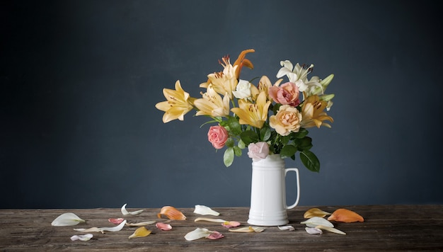 Bouquet of lily flowers in white jug on dark blue background