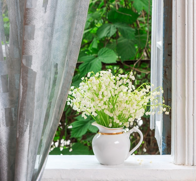 A bouquet of lily-of-the-valley flowers on a windowsill in a country house in the spring morning