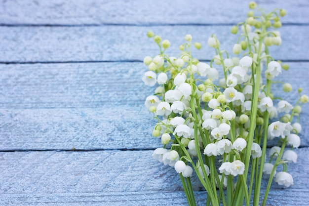 A bouquet of lily of the valley on a wooden background