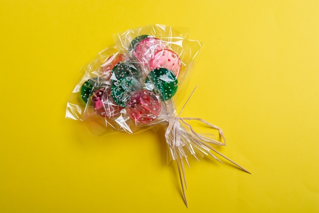 Bouquet of lollipops on a yellow background.