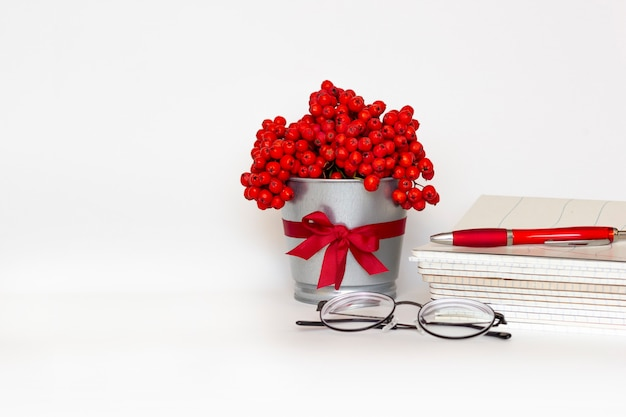 Bouquet of mountain ash in flower pot with satin ribbon, pile of notebooks, glasses and pen