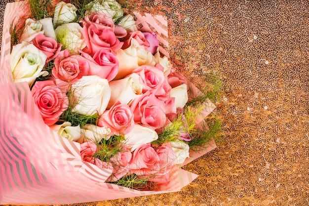 Bouquet of multicolor roses on a gold background as a gift for the valentine's day or wedding