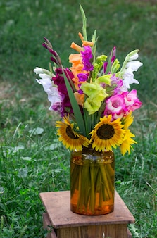 A bouquet of multicolored gladioli in a glass vase.