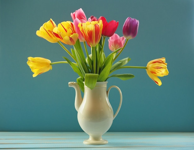 Bouquet of multicolored tulips in white ceramic tea pot