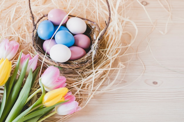 Bouquet near basket with eggs