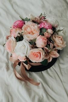 白いベッドのクローズアップの人工装飾花の花束