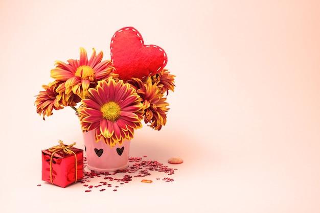 Букет из астр в подарочной коробке и красного сердца на кремовом фоне концепция праздника