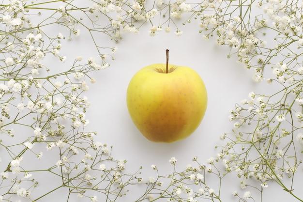 赤ちゃんの息やカスミソウと白い背景の上の黄色いリンゴの花束