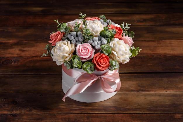 ギフトの円筒形の段ボール箱に美しい明るいバラの花の花束。石鹸の花のギフトブーケ