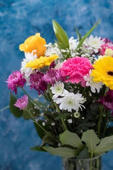 青い背景を持つ美しい花の花束