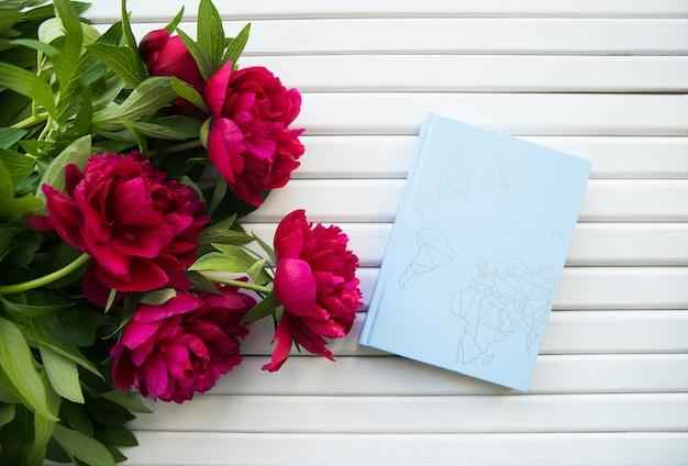 Букет красивых пионов лежит с голубой книгой
