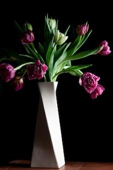 黒を背景に白い花瓶の美しいピンクグリーンのチューリップの花の花束ローキー