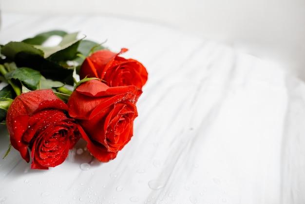 물으로 아름 다운 핑크 장미 꽃다발 대리석 테이블에 삭제