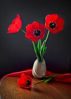 Букет красивых красных тюльпанов в небольшом весе концепция дня святого валентина, женщин или матери. натюрморт, выборочный фокус.