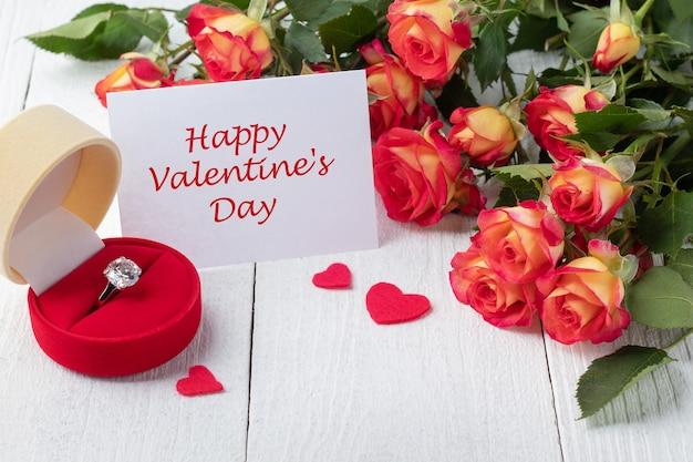 白い木製のテーブルの上の美しいバラ、婚約指輪、バレンタインカードの花束