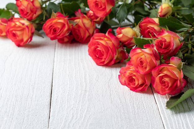 白い木製のテーブル、テキスト用のスペースに美しいバラの花束。休日のお祝い