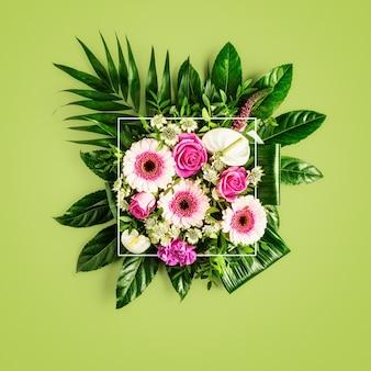 美しい春の花と白いフレームの花束。緑の背景にクリエイティブなレイアウトとフラワーアレンジメント。上面図、フラットレイ。花のデザイン、自然の概念