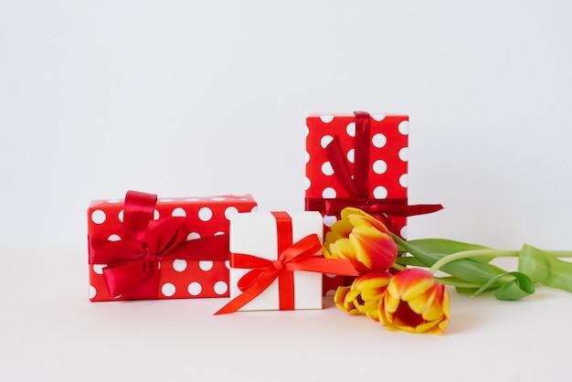 花瓶と明るい背景のテーブルの上のギフトボックスの美しい春のチューリップの花束。バレンタイン・デー