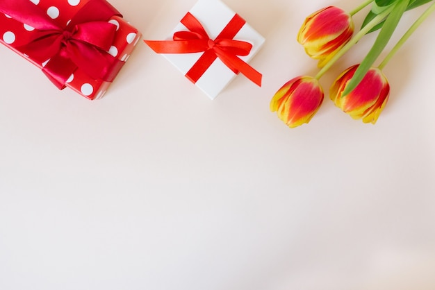 Букет красивых весенних тюльпанов в вазе и подарочной коробке на столе на светлом фоне.
