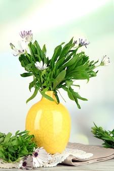 色の花瓶、木製のテーブル、明るい表面の美しい夏の花の花束