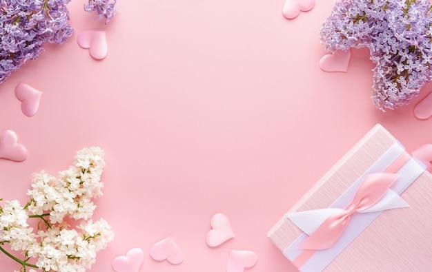 Букет из красивой белой и фиолетовой сирени, подарочной коробки и сердечек на розовом фоне. вид сверху. праздничная открытка с пионом на свадьбу, день святого валентина и матери.