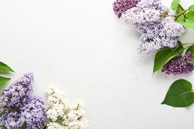 회색 배경에 아름다운 흰색과 보라색 라일락의 꽃다발. 평면도. 결혼식, 행복한 여성의 날 발렌타인, 어머니의 날을 위한 모란이 있는 축제 인사말 카드.