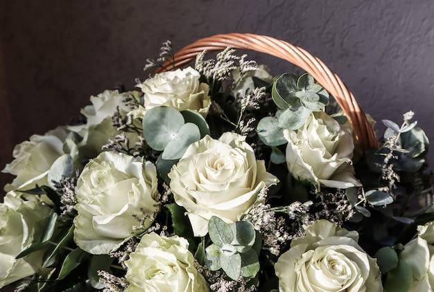 グリーティングカードに最適な暗い背景の籐のバスケットに美しい白いバラの花束