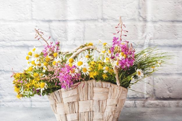 Букет красивых полевых цветов в корзине на сером фоне с копией пространства.