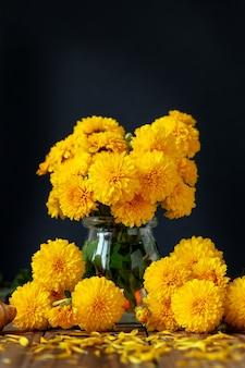 Букет из красивых желтых хризантем на деревянном столе на черном фоне. осенний цветочный натюрморт фон