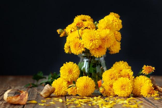 木製のテーブルの上の美しい黄色の菊の花束