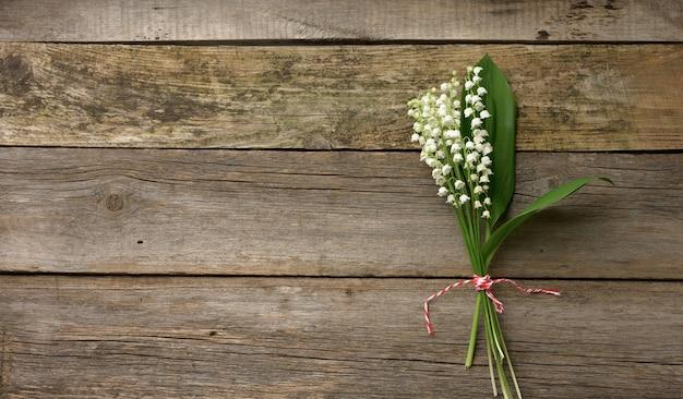 Букет цветущих ландышей на серой деревянной поверхности, вид сверху, копия пространства