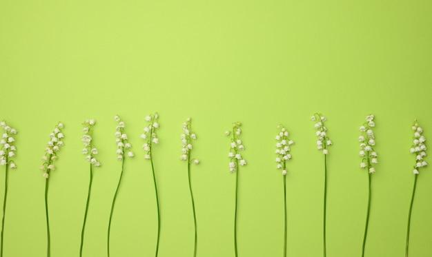Букет цветущих ландышей на зеленой поверхности, вид сверху. красивая поверхность для поздравительной открытки, копией пространства