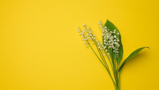 Букет цветущих ландышей на желтой поверхности, вид сверху, копия пространства